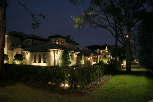Popular Choices for Designing Electrical Service This Spring - A home's yard at night, with accent lighting for the walls and hedge